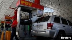 A worker walks next to a fuel dispenser at a gas station, in Caracas, Venezuela, Aug. 29, 2014.