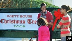 US First Lady Michelle Obama and her daughter Sasha are presented with the official White House Christmas Tree at the North Portico of the White House in Washington, DC, 27 Nov 2009