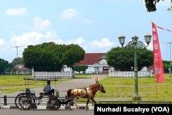 Sebuah andong wisata melintas di Alun-Alun Utara Yogyakarta. (Foto: VOA/Nurhadi Sucahyo)