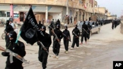 FILE - This undated photo posted on a militant website Jan. 14, 2014, shows Islamic State fighters marching in Raqqa, Syria.