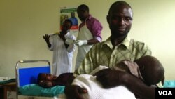 Savio Niwagaba of Uganda holds his newborn baby as his wife Chrisente, behind him, has a contraceptive implant placed in her arm