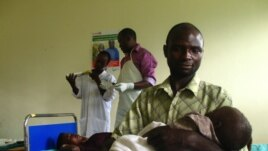 Savio Niwagaba holds his newborn baby as his wife Chrisente, behind him, has a contraceptive implant inserted in her arm, Kanungu, Uganda, June 19, 2012. (VOA / Hilary Heuler)