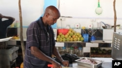 In this photo taken, Tuesday May, 22, 2012 Ahmed Jama chops meat and vegetable at one of his restaurants in Mogadishu, Somalia.