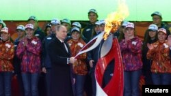 Rusiya prezidenti Vladimir Putin Soçi Qış Olimpiya Oyunlarının başlanğıcını qeyd edən mərasim zamanı olimpiada məşəlini alovlandırır. 6 oktyabr, 2013.