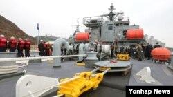 26일 한국 해군들이 신형 구조함인 통영함에서 예인기를 시연해보이고 있다.