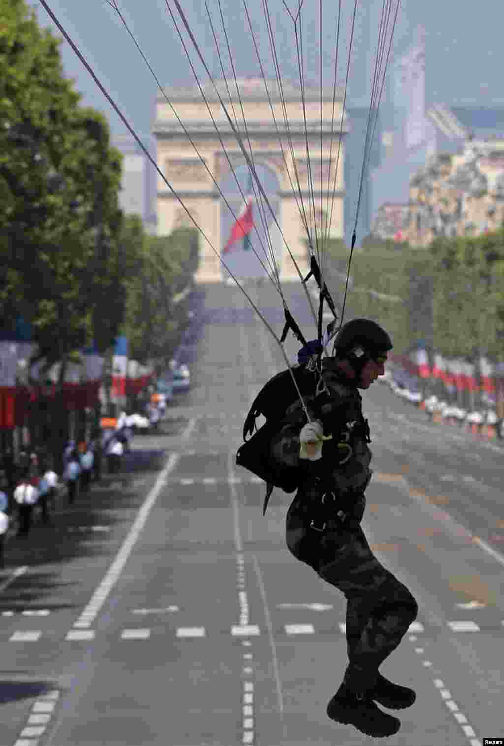 A parachutist lands in front of the reviewing stand on the Place de la Concorde during the traditional Bastille Day parade in Paris, July 14, 2013.