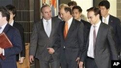 2012年10月25日,负责东亚和太平洋事务的美国助理国务卿坎贝尔(中左)在东京和美驻日大使鲁斯交谈,他们会晤了日本外交官员之后离开会场。
