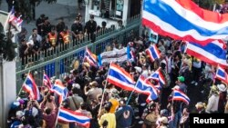 Anti-government protesters stand at the gate of the Customs Department office in Bangkok during a protest, Jan. 14, 2014.