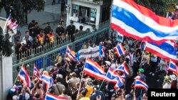 Para demonstran anti-pemerintah berdiri di gerbang kantor bea cukai di Bangkok (14/1). (Reuters/Nir Elias)