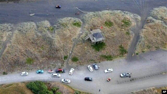 Ambulans dan kendaraan darurat diparkir di pantai Muriwai defat Auckland, Selandia Baru, Rabu (27/2). Seorang pria ditemukan tewas di lepas pantai ini akibat serangan ikan hiu. (AP Photo/New Zealand Herald, Chris Gorman)