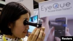 """Phoebe Yu mendemonstrasikan cara kerja alat """"VisionCheck 2"""" dari EyeQue (Foto: REUTERS/Rick Wilking)."""