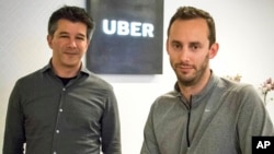 FILE - Then-Uber CEO Travis Kalanick, left, and Anthony Levandowski, co-founder of Otto, pose in the lobby of Uber headquarters, in San Francisco, Aug. 18, 2016. Uber said, in a June 22, 2017, court filing, that it hired Levandowski, a former Google engineer now accused of stealing trade secrets, even though the company knew he had information that didn't belong to him.