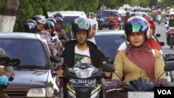Women on motorcycles in Aceh can be stopped by special Shariah police if they are deemed not to be properly covered, Dec. 7, 2014. (Zinlat Aung/VOA)