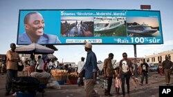 Watu wanapita mbele ya bango kubwa linaloonesha picha ya Rais Joseph Kabila