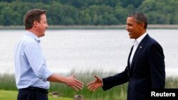 Britain's Prime Minister David Cameron (L) welcomes U.S. President Barack Obama on his arrival to the Lough Erne golf resort where the G8 summit is taking place in Enniskillen, Northern Ireland, June 17, 2013.