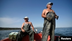 "Fisherman Panagiotis Pagonis, 72, (L) and his fellow fisherman Dimitris Karapetsas, 67, are seen onboard Pagonis' boat ""Katerina"" off the shores of Asprovalta, Greece, June 11, 2018."