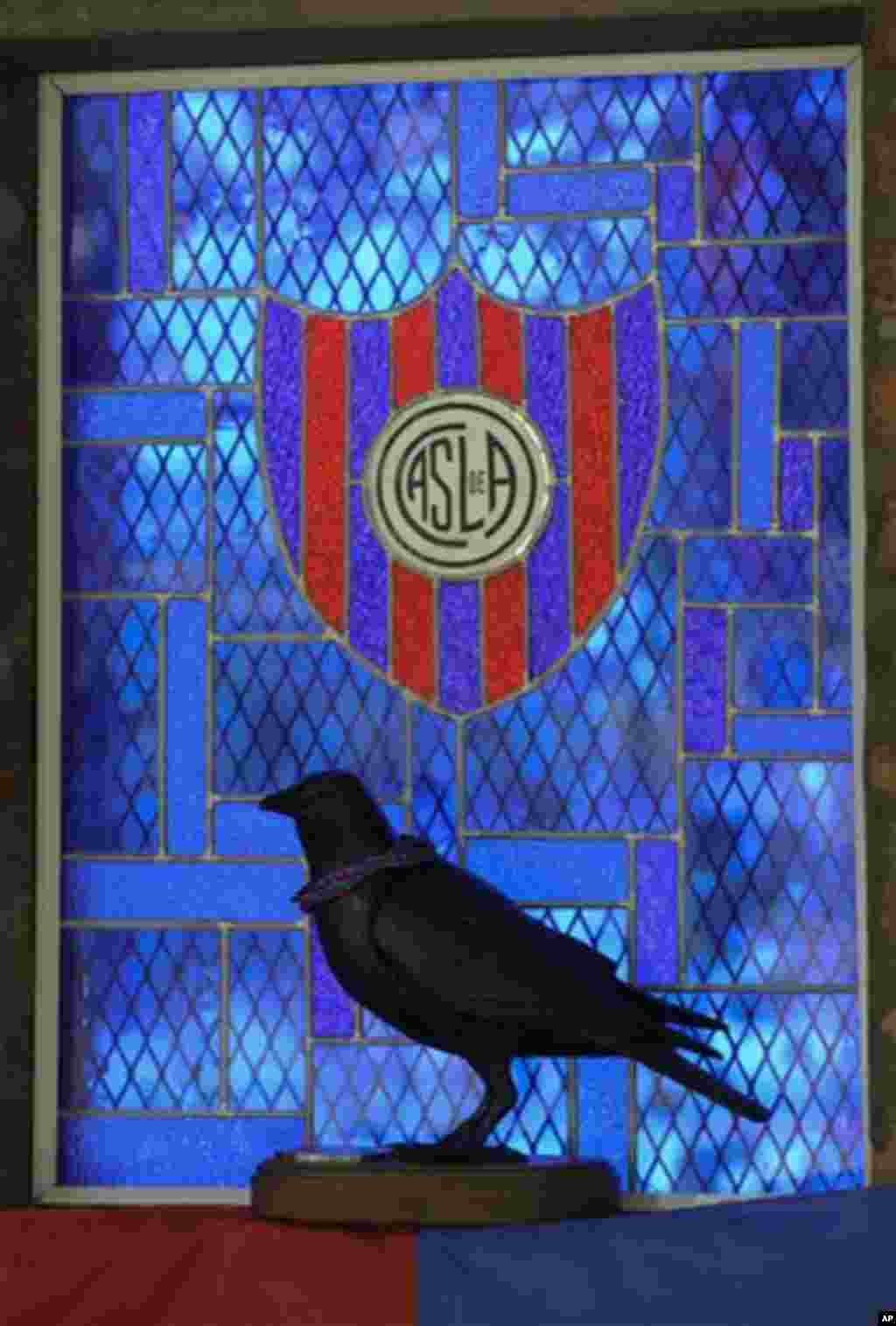 "A statue of a crow is silhouetted against the San Lorenzo de Almagro chapel window in Buenos Aires, Argentina, Thursday, March 14, 2013. The San Lorenzo soccer team is sometimes called the ""Crows,"" after the black color of a priest's robe."