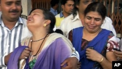 Unidentified relatives of an injured of a rebel attack cry outside a government hospital in Raipur, India, May 25, 2013.
