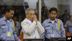 Former Khmer Rouge S-21 prison chief Kaing Guek Eav alias Duch (C) greets the court during his appeal hearing at the Court Room of the Extraordinary Chambers in the Courts of Cambodia (ECCC) on the outskirts of Phnom Penh February 3, 2012. The United Nati