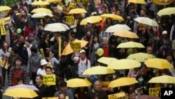 Người biểu tình đòi dân chủ mang theo những chiếc ô màu vàng và reo hò các khẩu hiệu kêu gọi cải cách bầu cử ở trung tâm Hong Kong, ngày 1/2/2014.