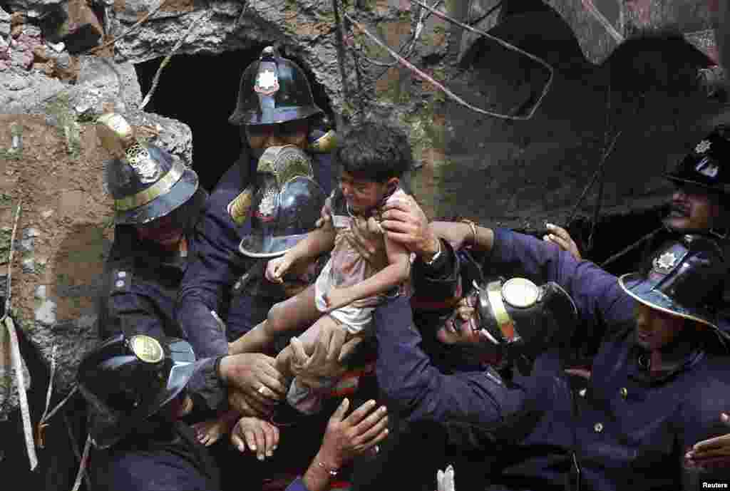Rescue workers carry a girl who was rescued from the rubble at the site of a collapsed residential building in Mumbai, India. The five-story apartment block collapsed in the financial center, killing at least eight people and trapping scores in the latest accident.