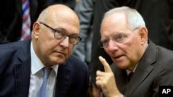 Menteri Keuangan Jerman Wolfgang Schaeuble, kanan, berbicara dengan Menteri Luar Negeri Perancis Michel Sapin dalam pertemuan meja bundar menteri-menteri keuangan zona euro di gedung EU Lex di Brussels, 12 Juli 2015.