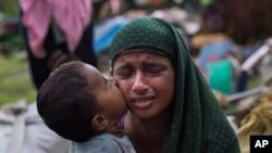 Seorang anak Rohingya Muslim mencium ibunya saat mereka beristirahat setelah melintasi perbatasan Myanmar dan Bangladesh di perbatasan dekat kawasan Teknaf Cox Bazar, 2 September 2017 (foto: AP Photo/Bernat Armangue)