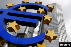 The euro logo sculpture is seen in front the headquarters of the European Central Bank in Frankfurt, Oct. 26, 2014.