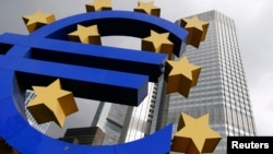 A euro logo sculpture is seen in front the headquarters of the European Central Bank in Frankfurt October 26, 2014.