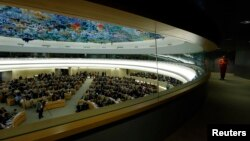 FILE - A staff member walks along a corridor during the 26th session of the Human Rights Council at the United Nations in Geneva, Switzerland, June 10, 2014.