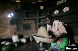 A woman prepare sorghum for food at her home in drought-hit Masvingo, Zimbabwe; REUTERS/Philimon Bulawayo