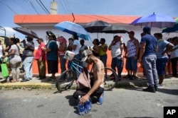 People affected by the passage of Hurricane Maria wait in line at Barrio Obrero to receive supplies from the National Guard, in San Juan, Puerto Rico, Sept. 24, 2017.