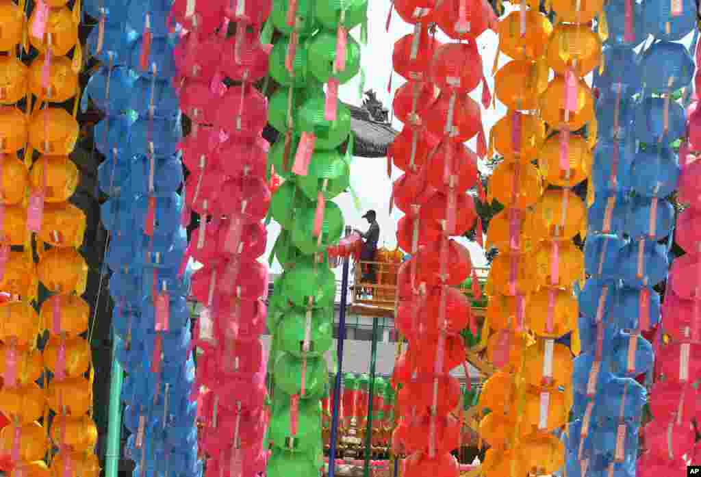 A worker removes lanterns following Buddha's birthday celebrations at the Chogye Temple in Seoul, South Korea. Similar lanterns are annually displayed in all Buddhist temples around South Korea for the public viewing.
