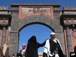 A woman walks past a fortified gate in Sanaa