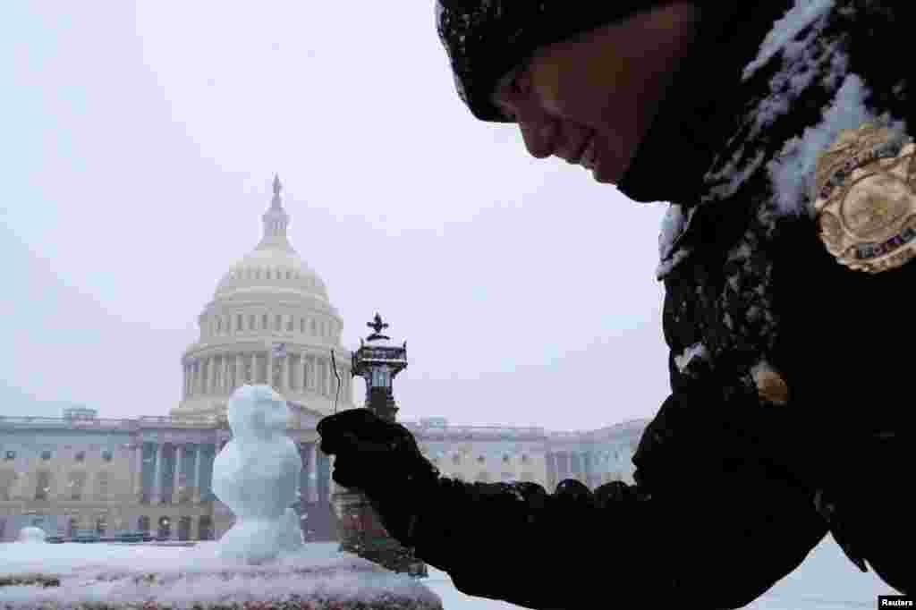 یک افسر پلیس ساختمان کنگره در واشنگتن پایتخت آمریکا مشغول تزئین این آدم برفی کوچک است.