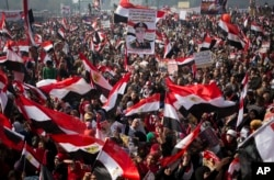 FILE- Egyptians wave national flags and hold pictures of Egypt's Defense Minister Gen. Abdel-Fattah el-Sissi, during a rally in Tahrir Square, in Cairo, Egypt, Saturday, Jan. 25, 2014. (AP Photo/Khalil Hamra)
