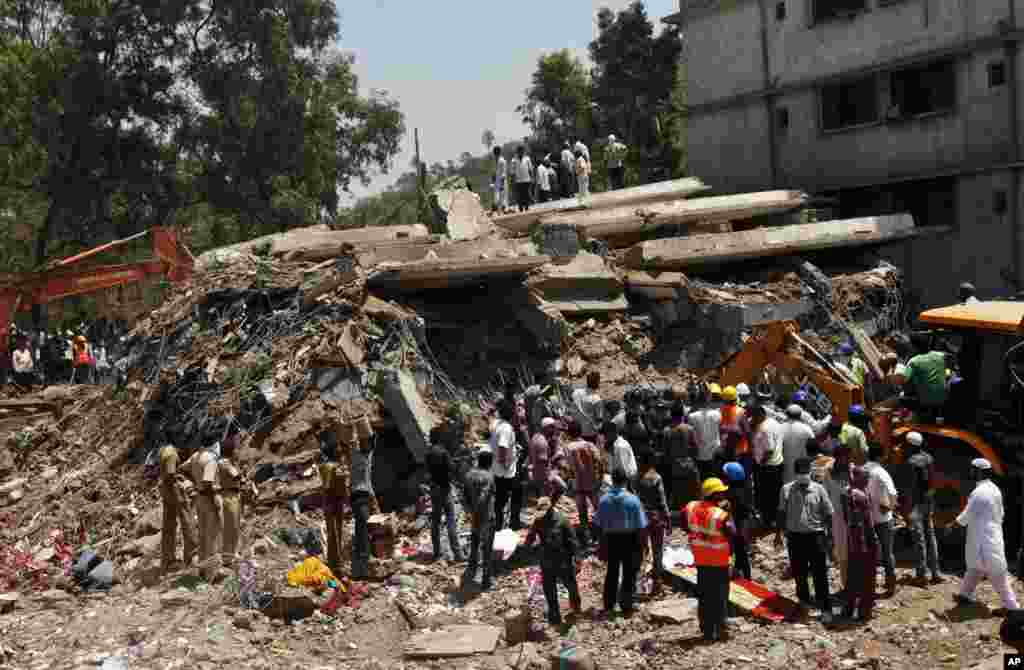 People gather around a collapsed building as a rescue operation continues on the outskirts of Mumbai, India, April 5, 2013.