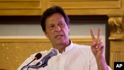 Pakistani opposition politician Imran Khan, chief of the Pakistan Tehreek-e-Insaf party, gives the victory sign during a press conference to present the party's manifesto for the forthcoming election, in Islamabad, Pakistan, July 9, 2018.