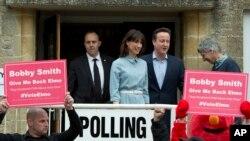 PM David Cameron dan istrinya Samantha usai mencoblos di TPS Spelsbury, Inggris disambut dengan protes oleh beberapa demonstran, Kamis (7/5).