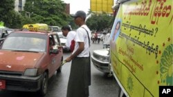 A member of the Democratic Party (Myanmar) hands out political booklets on the party to a taxi driver during their election campaign in downtown Rangoon, Burma, 19 Oct 2010