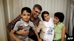 FILE - Iranian lawyer Nasrin Sotoudeh poses with her husband, Reza Khandan, her son Nima (L) and her daughter Mehraveh (R ) at her house in Tehran on Sept. 18, 2013, after being freed after three years in prison.
