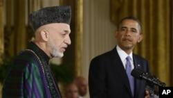 Presiden Barack Obama mendengarkan Presiden Hamid Karzai yang tengah memberikan penjelasan dalam konferensi pers di Gedung Putih, Jumat (11/1).