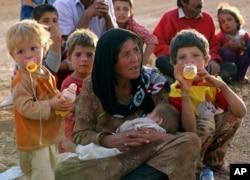 Một bà mẹ tỵ nạn Syria cùng con nghỉ chân tại cửa biên giới gần Suruc, Thổ Nhĩ Kỳ.