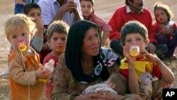 지난 25일 한 시리아 난민 여성이 터키와 접경지역에서 아이들과 휴식을 취하고 있다.