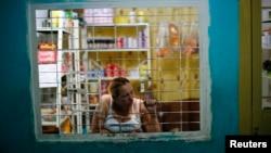 Una mujer cuida su tienda dentro de un edificio en Caracas.