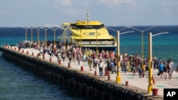 FILE - Tourists and passengers disembark from a ferry onto the wharf on Playa del Carmen, Mexico, March 2, 2018. The U.S. Embassy in Mexico has narrowed its travel warning for the city amid what it calls an unspecified security threat.