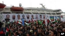 People holding Turkish and Palestinian flags cheer as the Mavi Marmara ship, in the background, the lead boat of a flotilla headed to the Gaza Strip which was stormed by Israeli naval commandos in the Mediterranean May 31, 2010, returns to Istanbul, Turkey.
