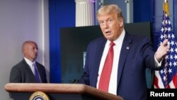 Moko na bayi bokengi na loboko ya mobali ya président Donald Trump, na bokutani na bapanzi sango na Maison Blanche, Washington, D.C., 10 août 2020.