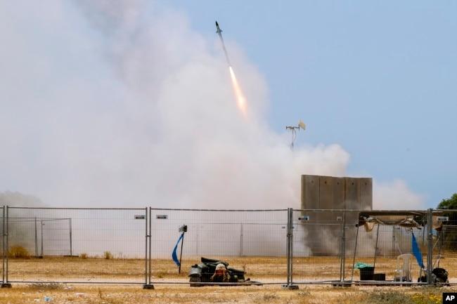 Seorang tentara Israel berlindung saat rudal dari sistem anti-pesawat Iron Dome lepas landas untuk mencegat roket dari Jalur Gaza di Ashkelon, Israel selatan, Selasa, 11 Mei 2021. (AP Photo / Ariel Schalit)