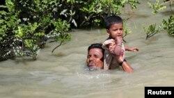 Seorang pengungsi Rohingya menggendong anaknya sambil berenang menyeberangi sungai di perbatasan Rakhine, Myanmar dan Palang Khali, Bangladesh (foto: dok).